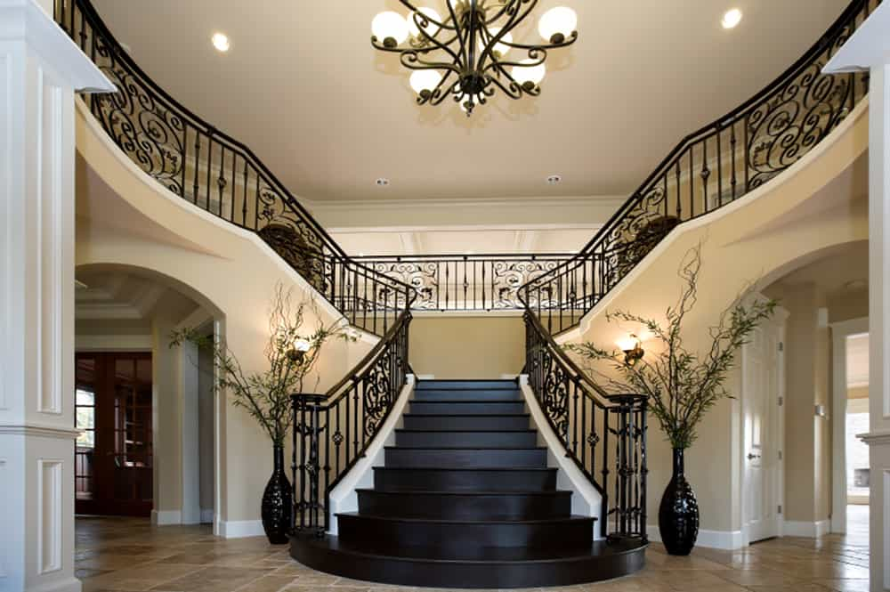 The dual staircases that merge into a single point are seriously impressive. The bottom is flanked by dual vases with branches. archways lead to different rooms of the home on either side of the stairs.