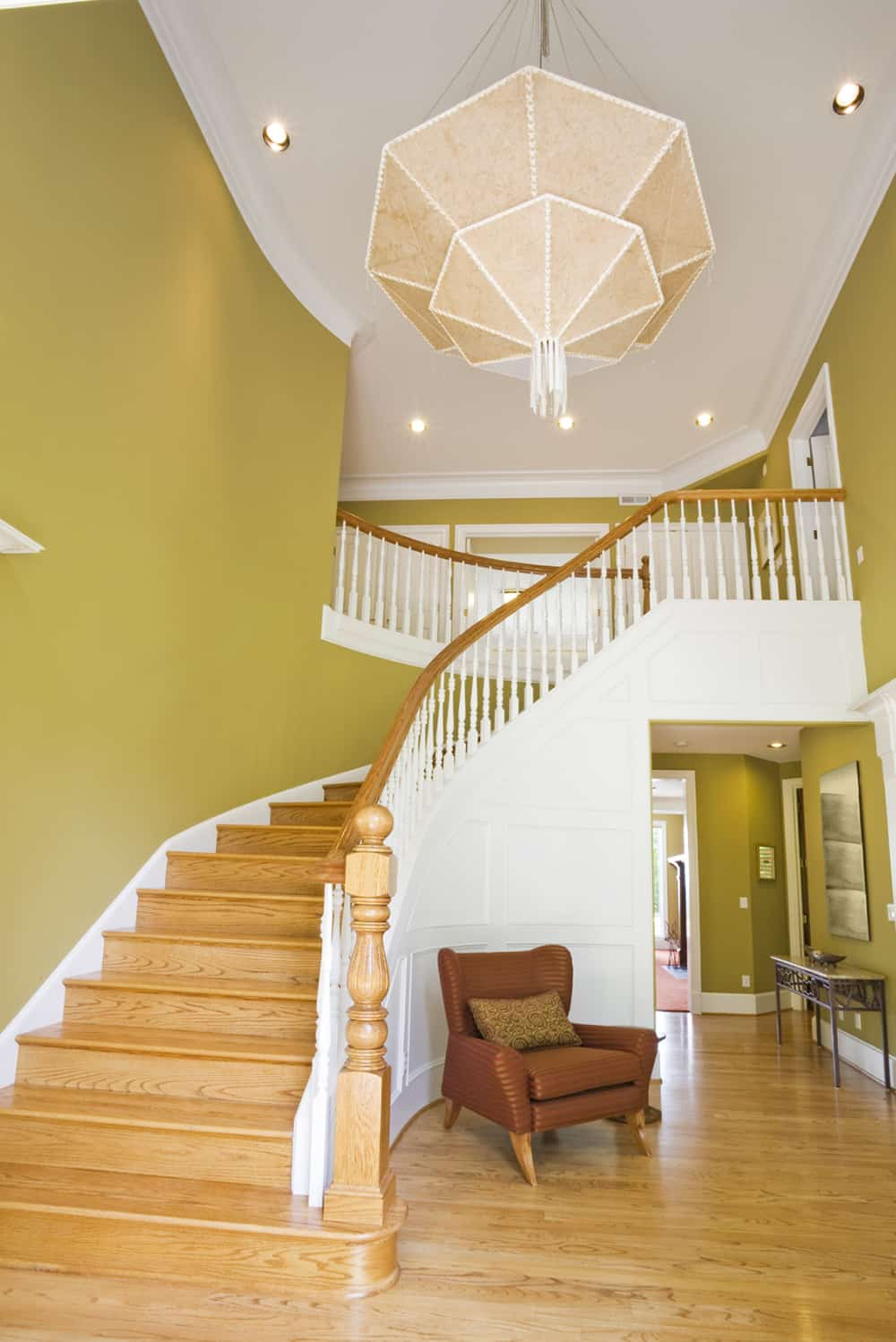 At the top of this soaring foyer is a unique chandelier, which dominates the entire space. The curve of the stairs is bedecked in wainscoting.