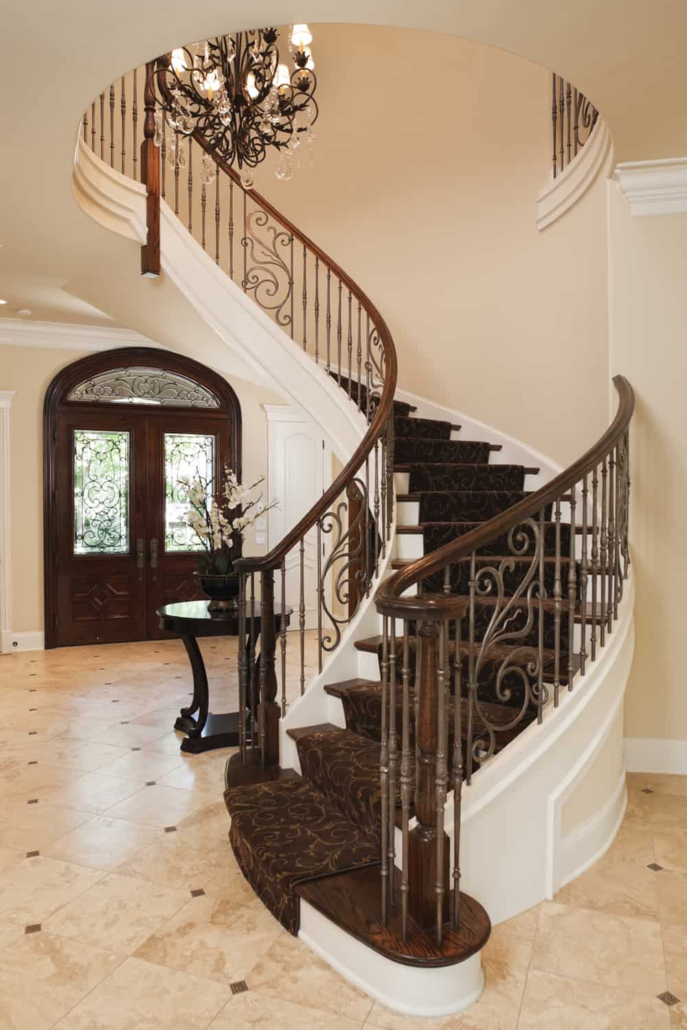 At the center of this spacious foyer is a spiral staircase up the next floor, complete with a floral chandelier.