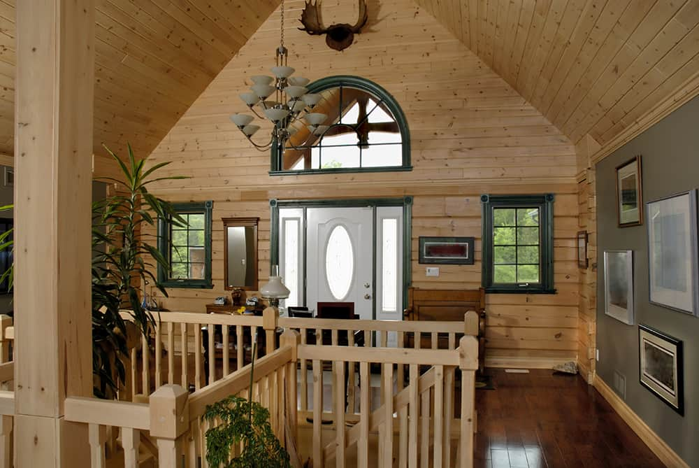 The interior of this home is filled with natural pine, giving this spacious entryway a cabin-like feel. Accents of rich forest green and a few houseplants add to the natural atmosphere.