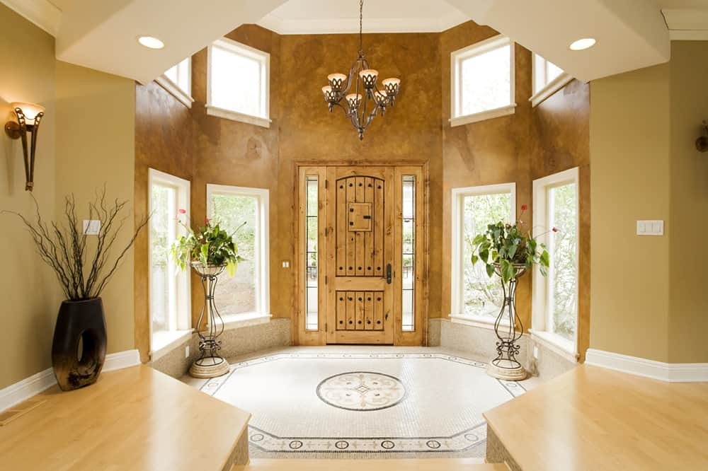 The transition between the hallway and the foyer is marked by a change from the heavily textured bronze in the hexagonal foyer to a softer yellow-brown in the hallway beyond.