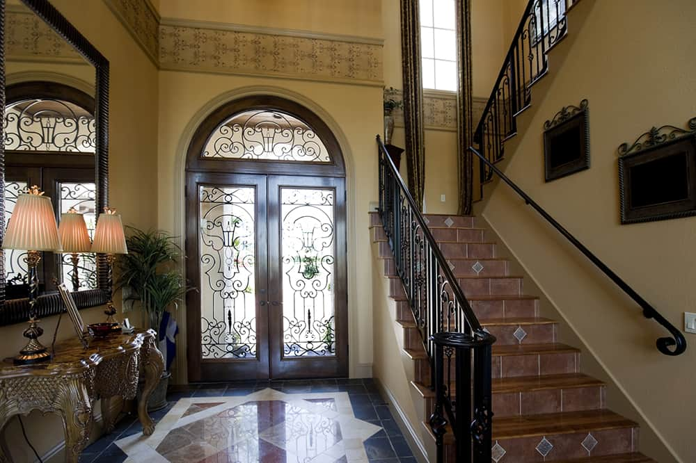 Richly colored tile work and iron scroll work in both the door and on the banister make this traditional foyer welcoming.