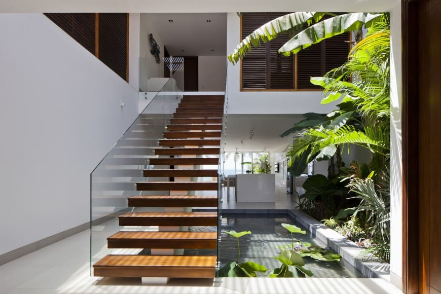 The foyer of this home is light and bright, with a small pond and a garden bed inside the home. A floating staircase with glass balustrades leads up to the second floor of the home.