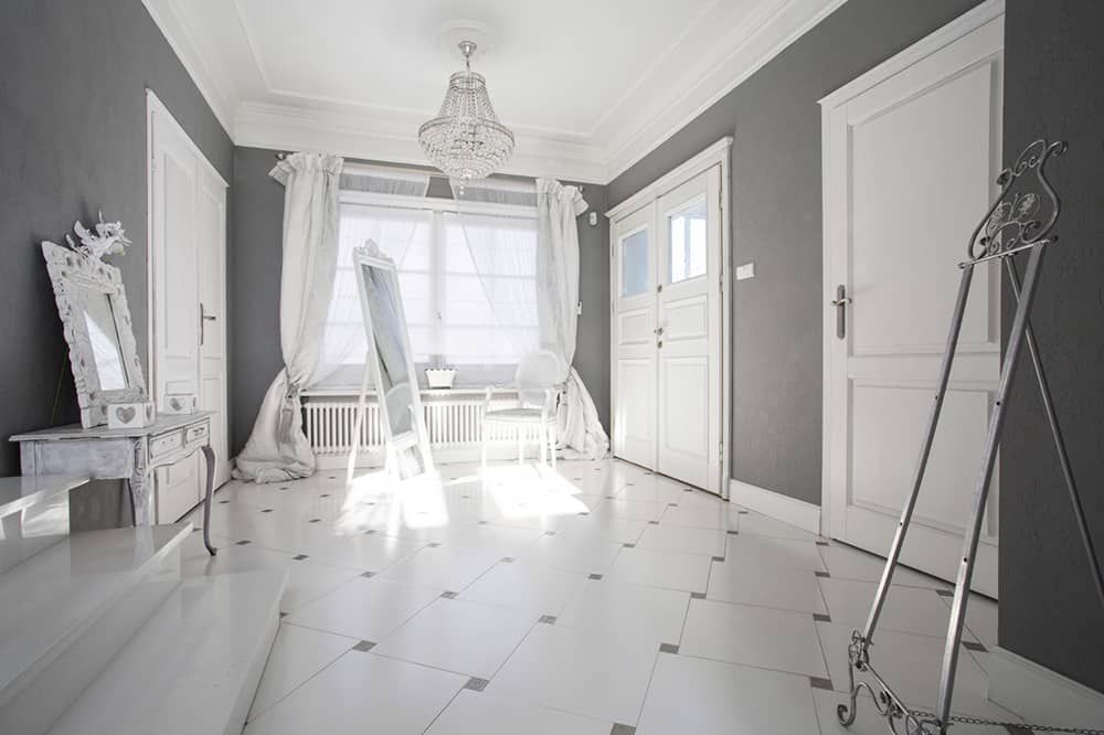 Deep charcoal walls and white floors, ceiling, and accents make for a starkly contrasting room. Softer fabrics contrast with cold metal for additional contrast.