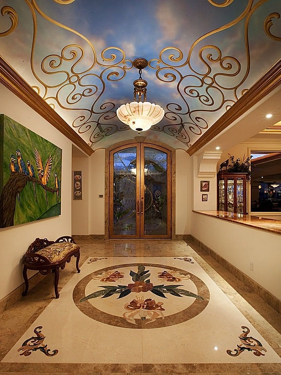 This is an incredibly impressive foyer that features a custom photo ceiling that depicts a cloudy sky above golden scrollwork. Also of note is the mosaic floor, which breaks up the solid tile with floral depictions.