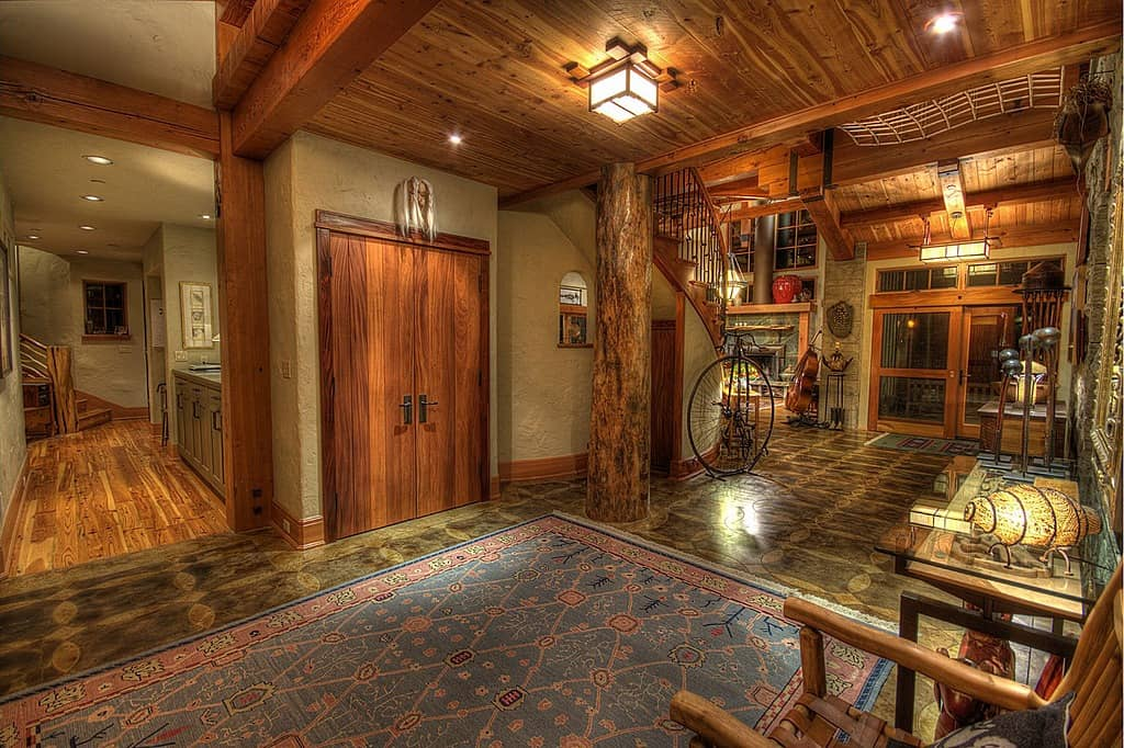The sheer amount of natural wood in this foyer is more than enough to label it as rustic, but the addition of antique accessories adds to the rustic atmosphere.