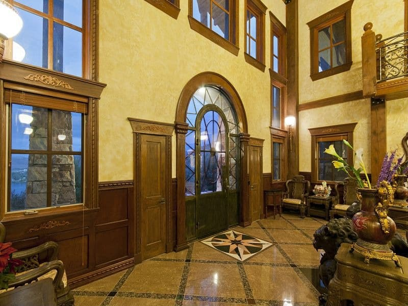 The space in this unique foyer is incredible. The home features an enormous glass door with sunburst detailing in the glass. The door is flanked by two simpler doors; one on either side. Almost a dozen windows adorn the space, letting in copious amounts of light.