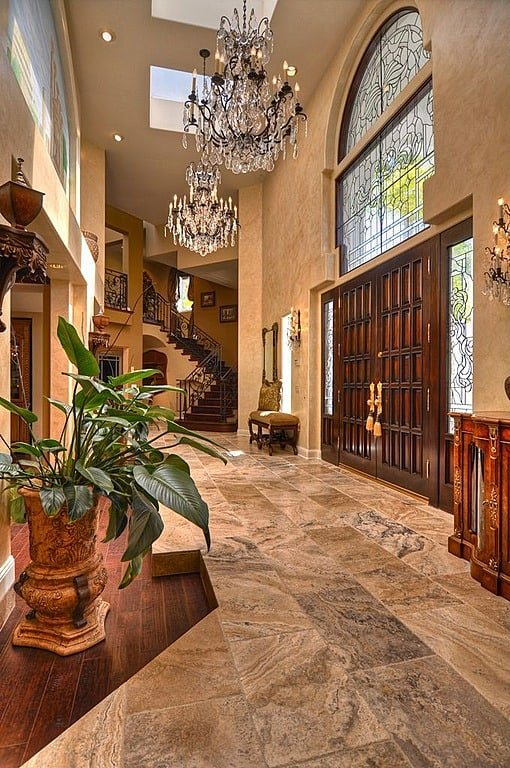The veining in the tile, skylights, dual chandeliers, and incredible, ornate windows make this sizable entryway one you'd never forget.