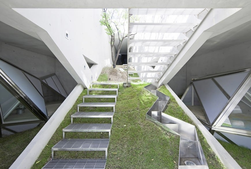 This is an incredibly unique foyer in an amazing residential home. Upon entering, you are greeted by metal stairs, grass, trees, and drainage channels.