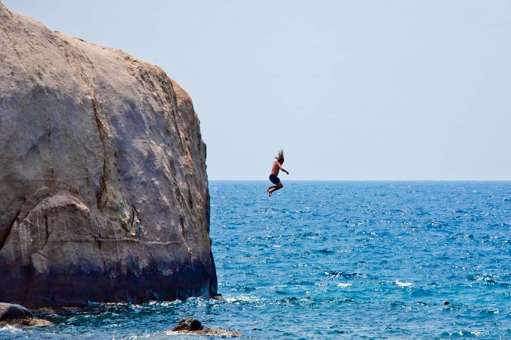Man jumping off cliff into the sea