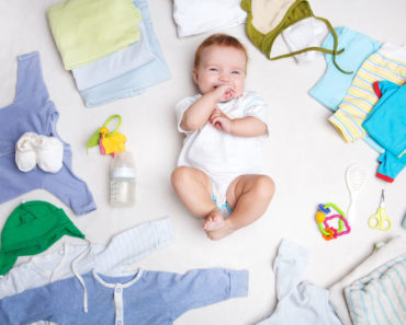 A baby surrounded with baby clothes.