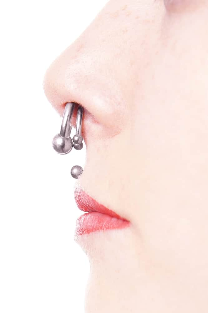 Lower side profile of a woman with double nostril piercing.