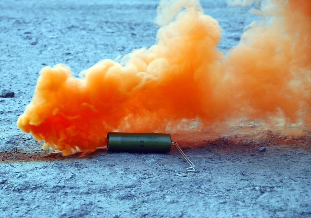 Orange smoke bomb exploding on the ground.