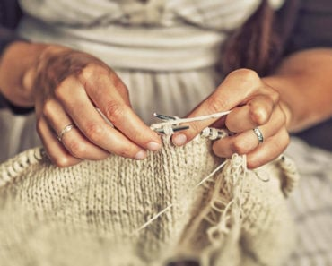 A closer shot of an old woman knitting an off-white yarn.