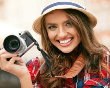 A beautiful tourist, smiling while holding a camera.