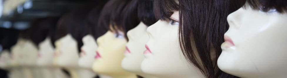Different styles of wigs worn by different mannequins.