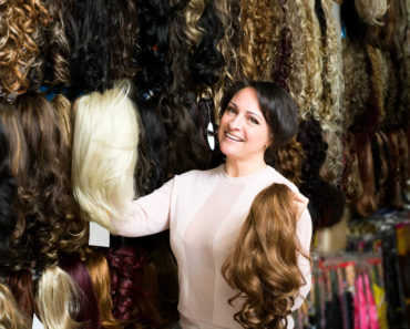 A middle-aged woman assisting in a wig store.