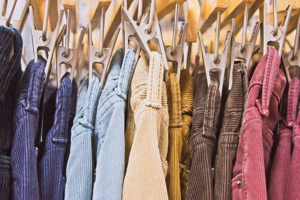 A set of multi-colored corduroy pants on cloth hangers.