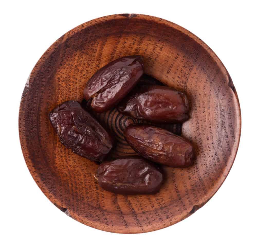 Five pieces of Halawai dates served in a wooden plate.