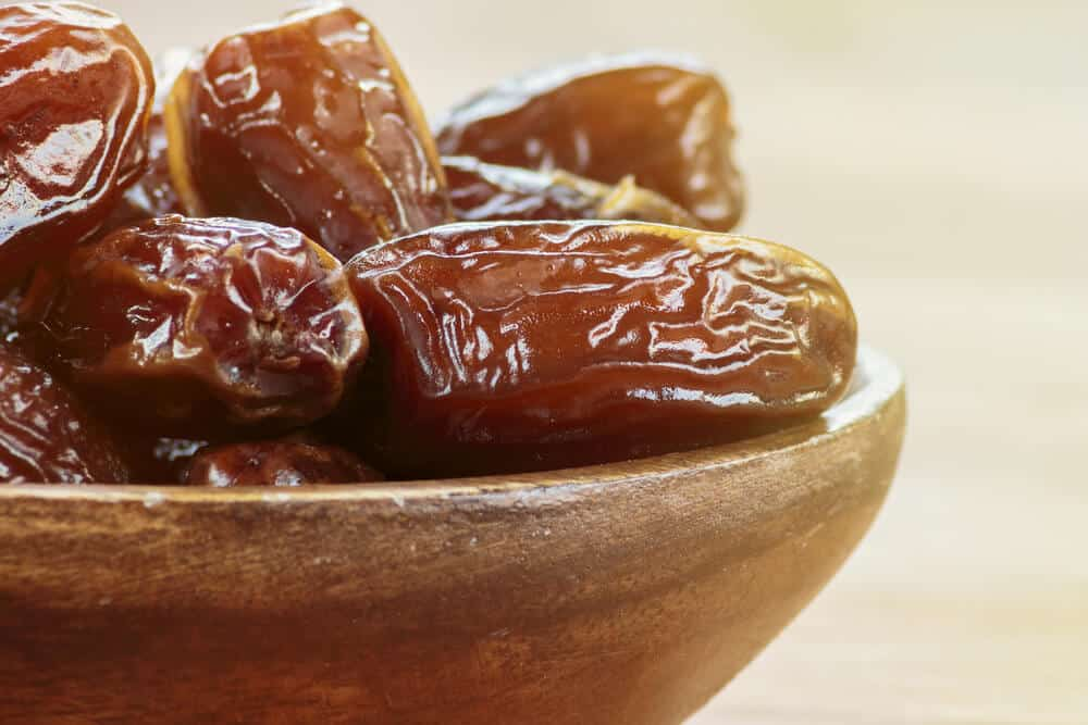 A close-up shot of semi-soft dates served in a wooden bowl.