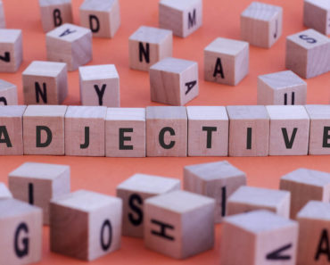"The word ""adjective"" formed using scrabble pieces."