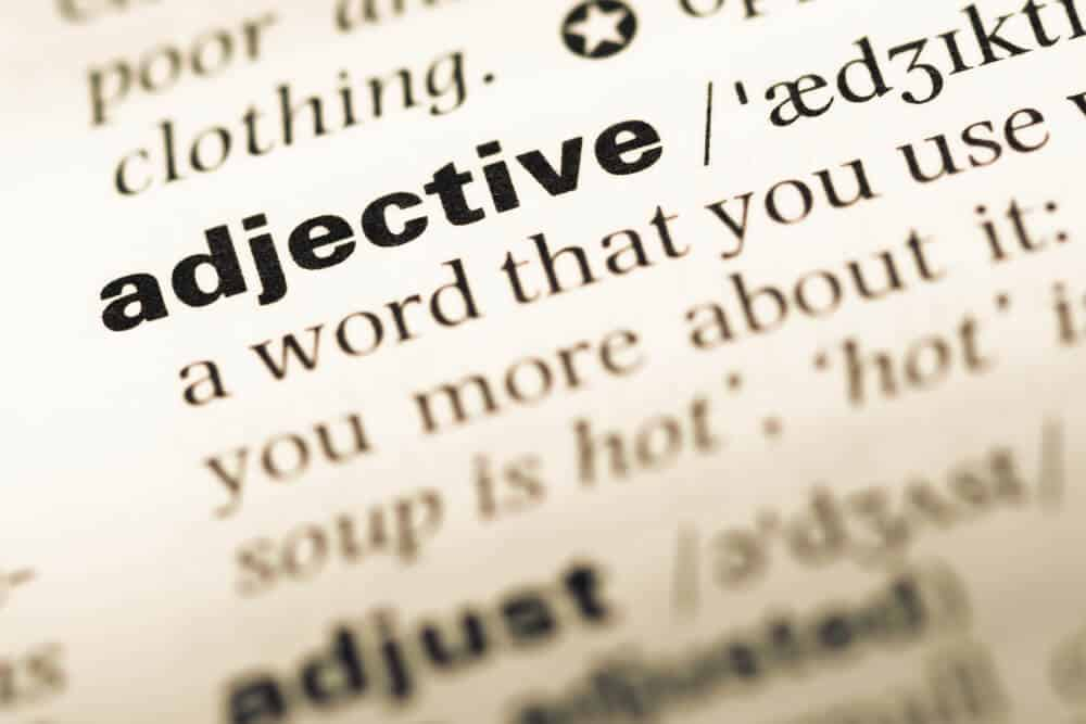 A close-up shot from the dictionary of the word adjective.