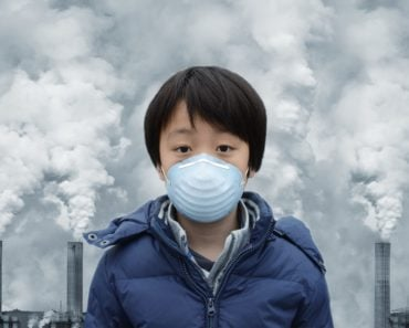 A boy wears a face mask to shield himself from the harmful effects of toxic gases that are emitted by factories.