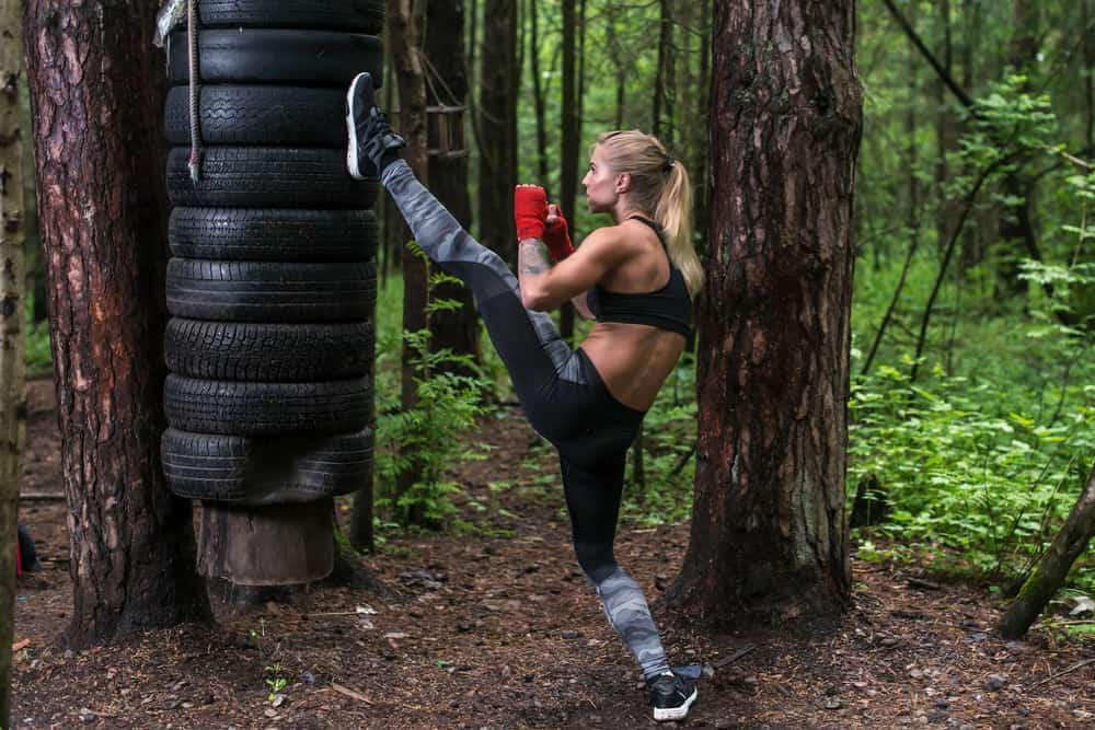 A woman practices her axe kick outdoors.