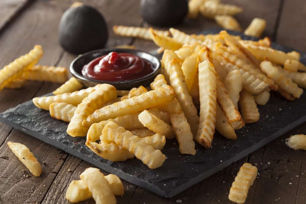 Crinkle fries with ketchup on the side.