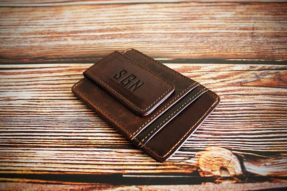 A money clip wallet made of brown leather.