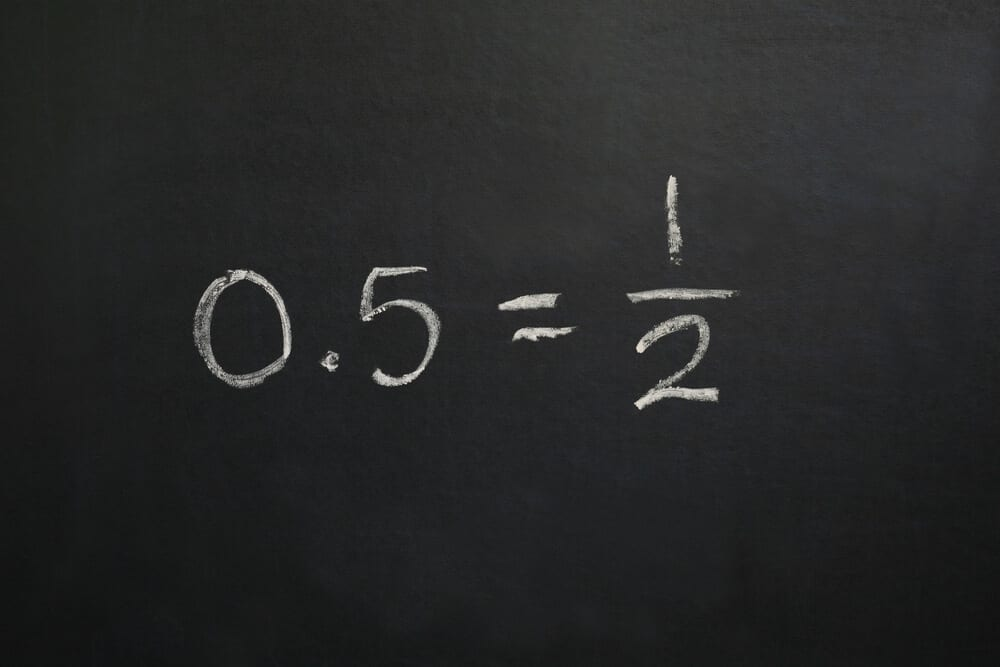 A fraction with its equivalent decimal, written on a black board.