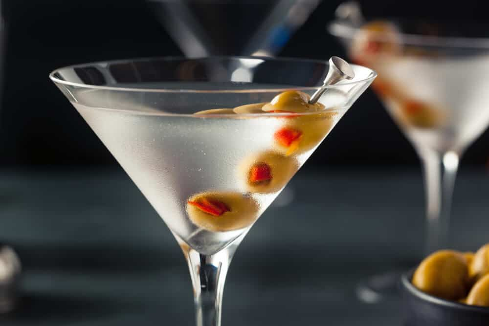 A glass of dry martini with olives.