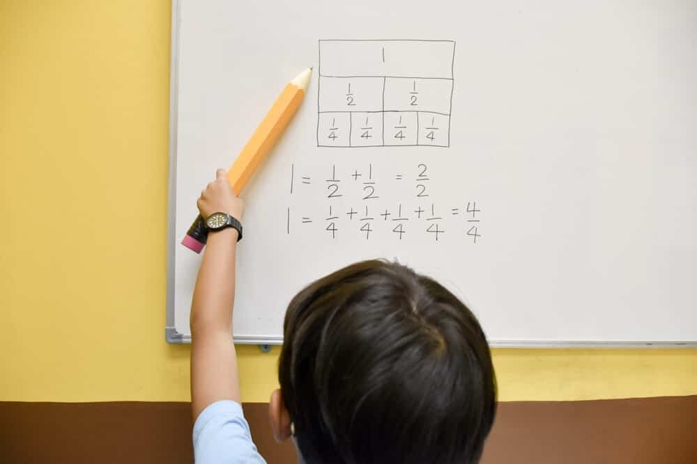 A kid writing down some equivalent fractions on a whiteboard.