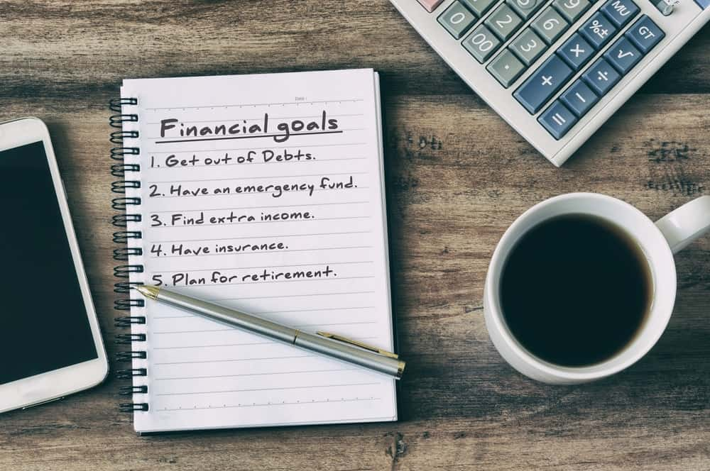 A smartphone, calculator, and a cup of coffee surrounds a notebook with a list of Financial goals written on it and a pen resting above it.