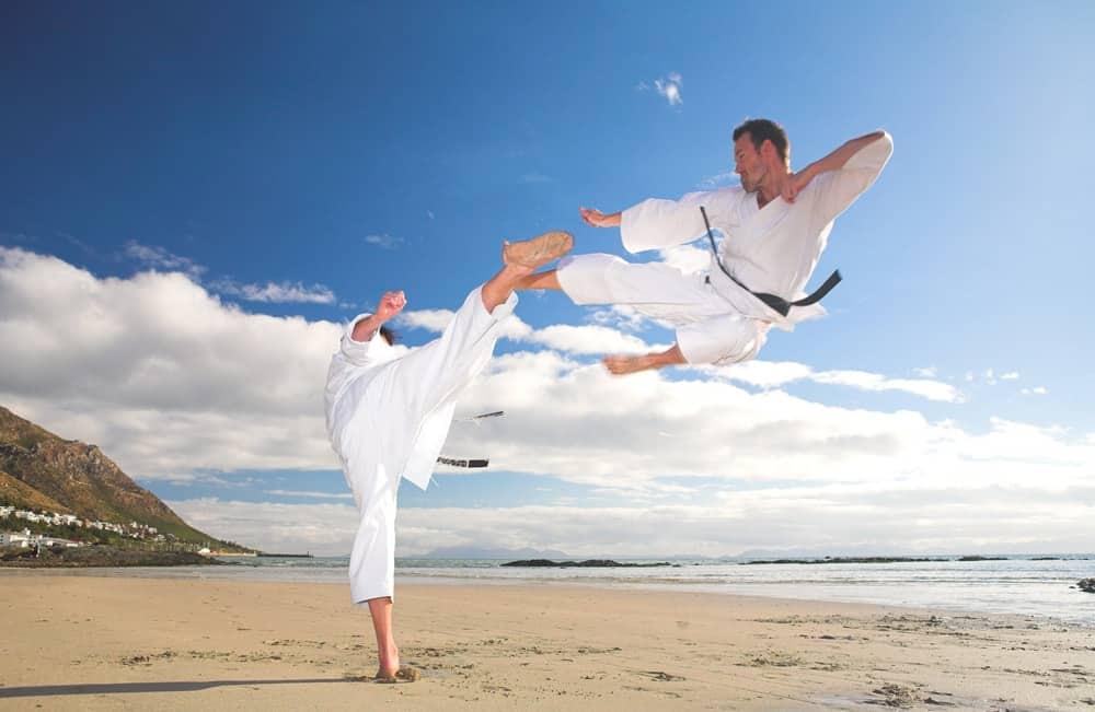 A male taekwondo athlete demonstrates the flying kick on the beach.