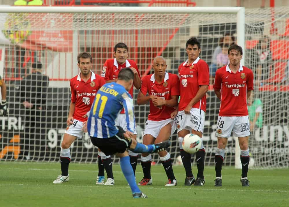 A football player gives a free kick during the last stages of the Spanish second division league match.