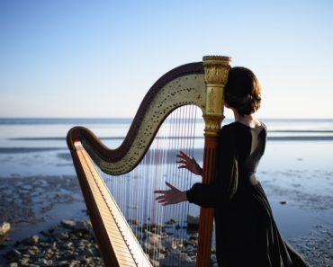 A lady plays her harp while facing the sea.