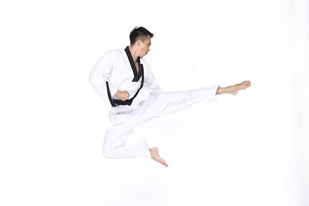 A taekwondo black belter shows how the jump kick is done.
