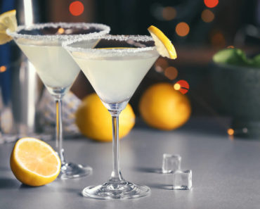 Lemon martini cocktails with sliced lemons.