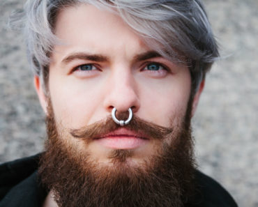 A close up shot of a man with a nose piercing.