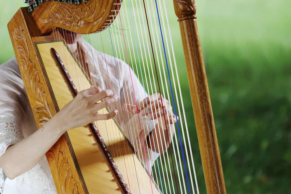 A golden paraguayan harp is being played outdoors.