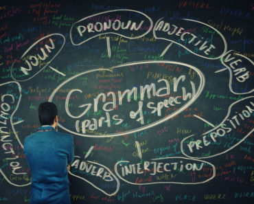 A man analyzing the parts of speech written on the blackboard.