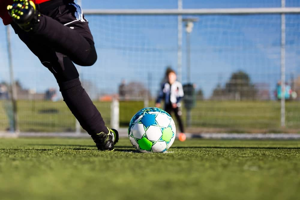 A soccer player is about to do his penalty kick in hopes of scoring a goal against the opponent.