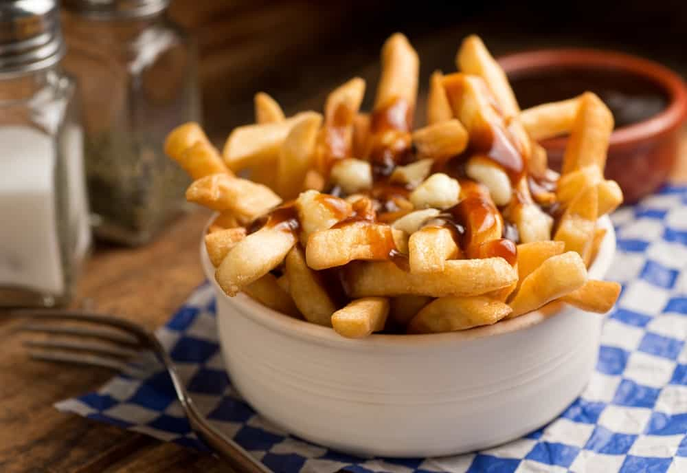 Poutine served on a white bowl.