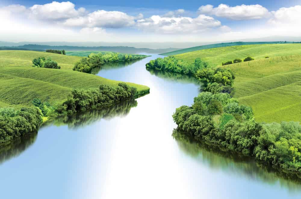 A zigzag river that flows between green valleys.