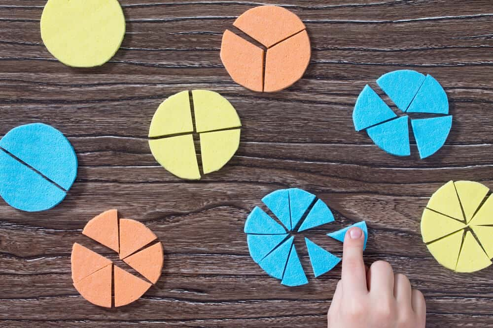 A child playing with colorful pie and fraction charts.