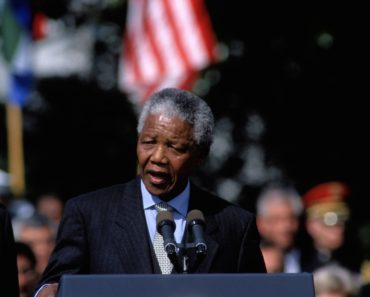 Nelson Mandela is a delivering a speech in front of a crowd. in Washington DC.