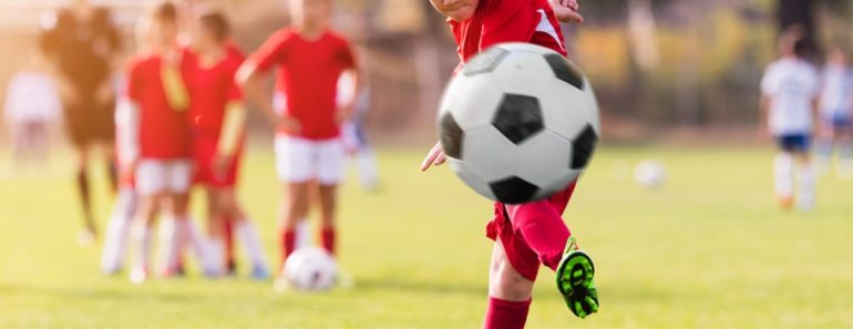 A young football player kicks the ball to score a goal.