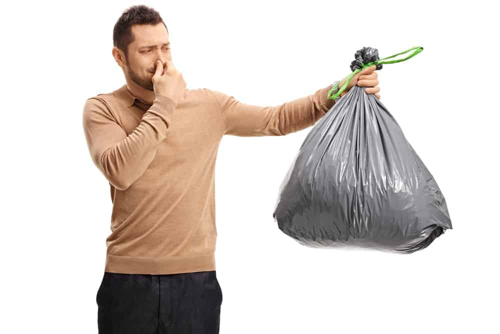 A man holds a garbage bag that emits an unpleasant odor.