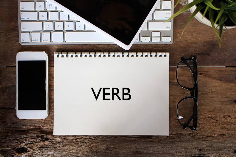 "The word ""verb"" written on a notebook placed on a table together with a laptop, a phone and a pair of eyeglasses."